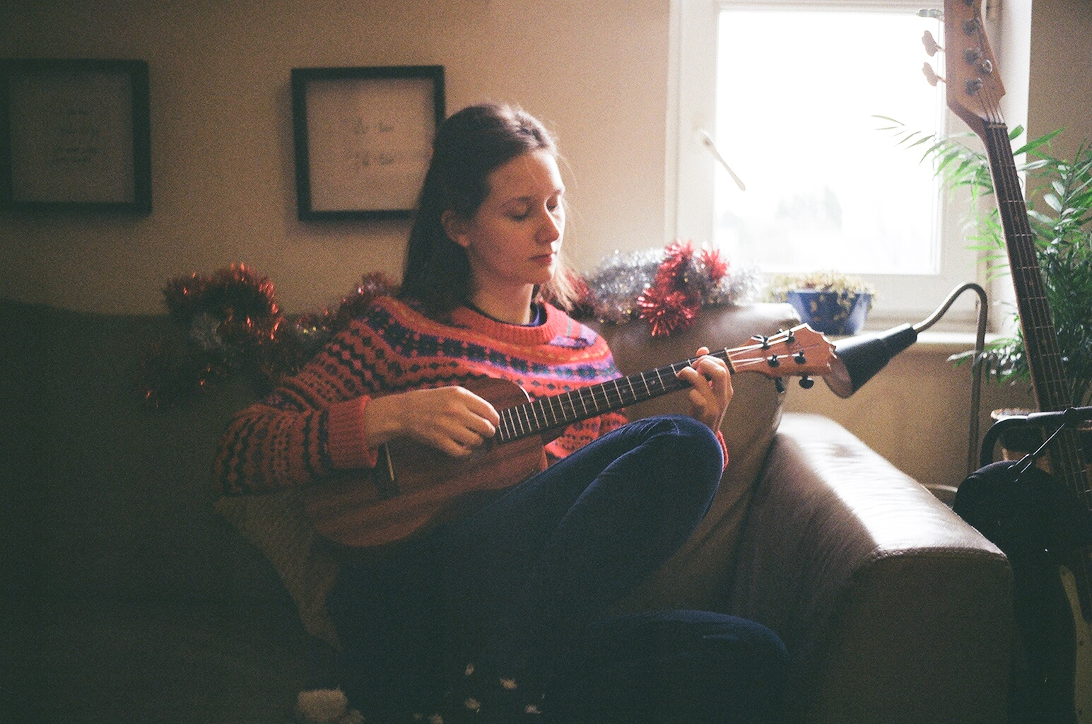 Eleanor in an arm chair playing the ukelele