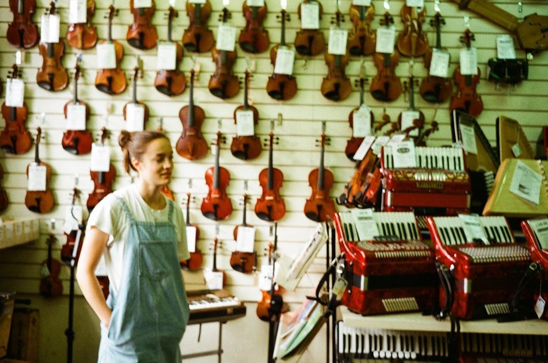 Georgia in a music shop with a wall full of violins
