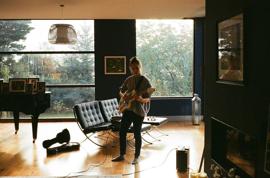 Georgia playing the guitar in a light spacious room with trees outside