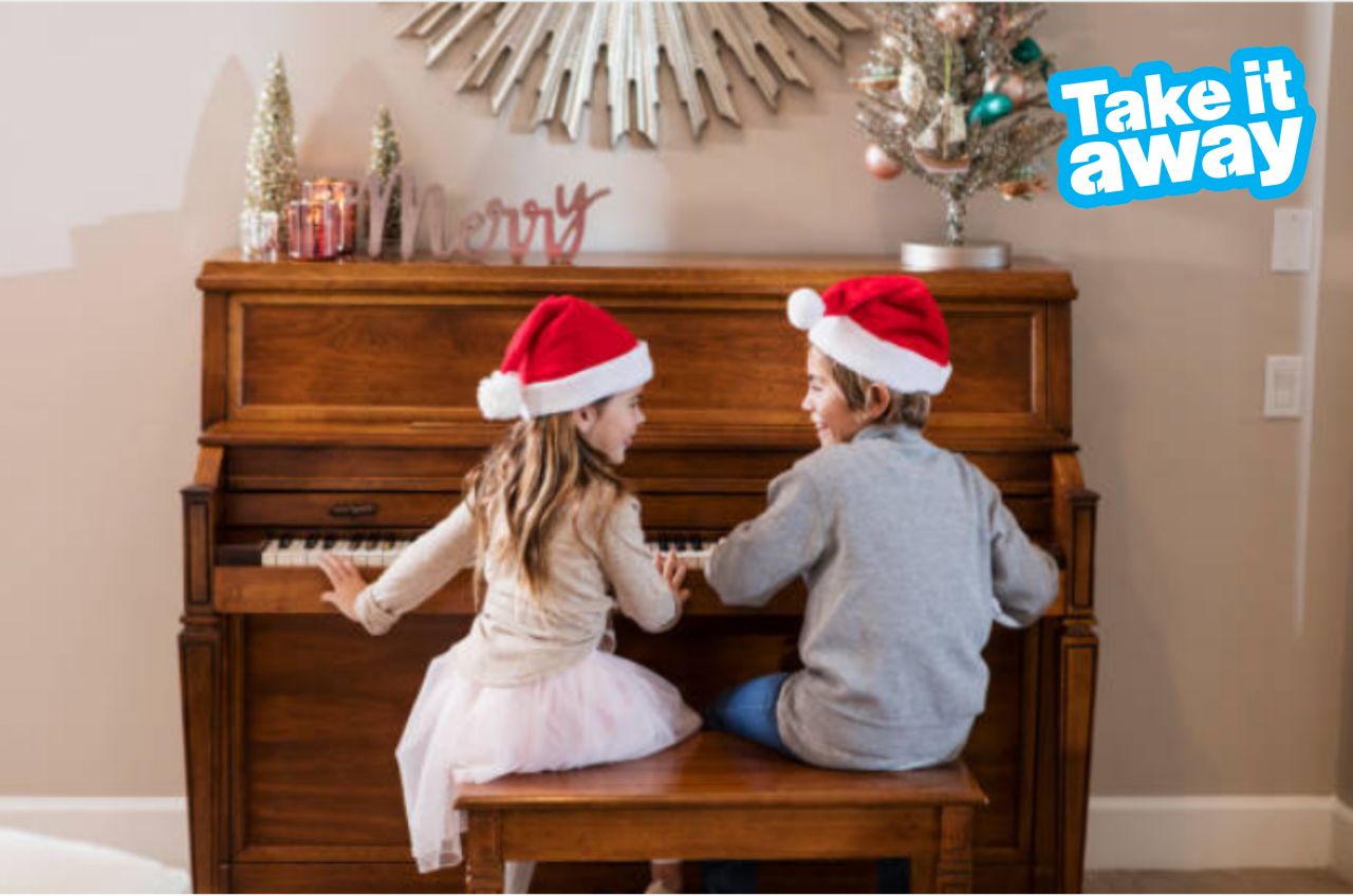 two children wearing Christmas hats playing the piano