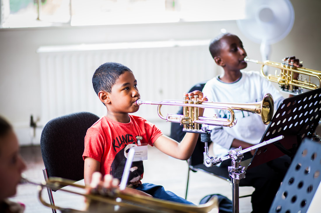 two young boys playing one-handed trumpets
