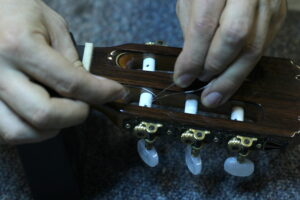 securing guitar strings back in tuning pegs