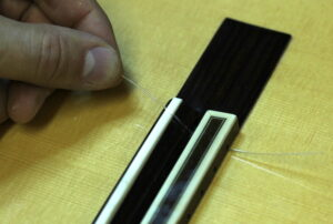 Tying a new E string at base of guitar