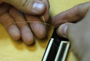 tying new guitar string at base of guitar