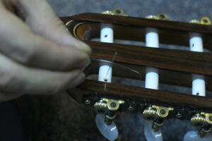 securing guitar strings back into tuning pegs